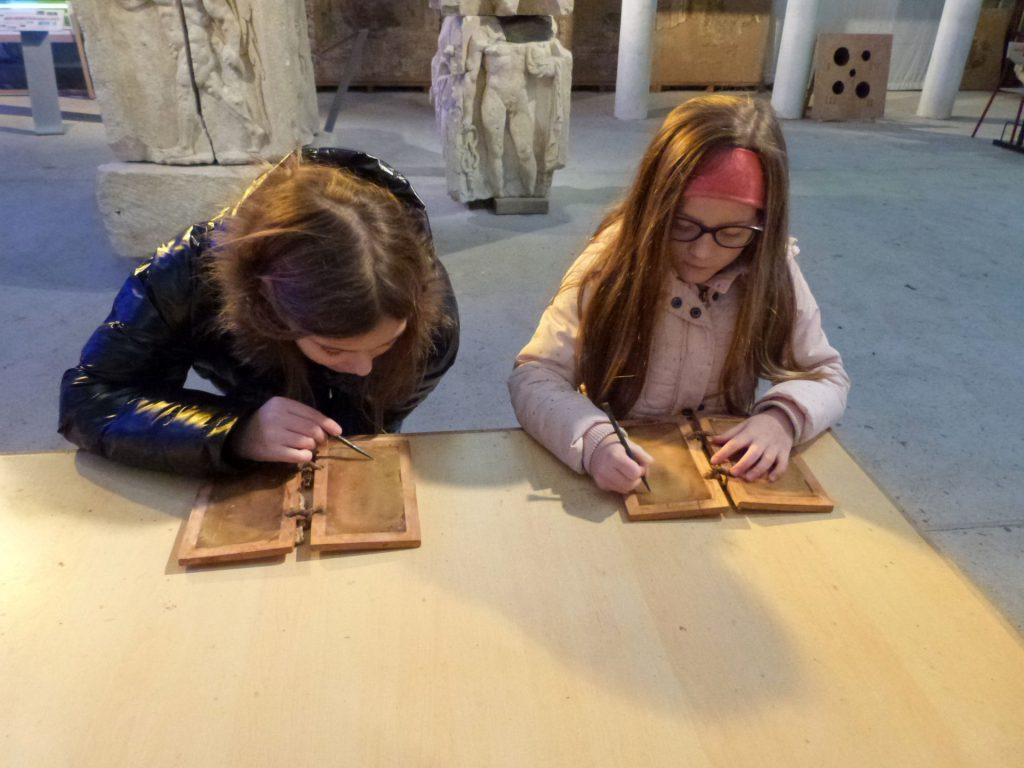 2 jeunes élèves écrivent sur des tablttes